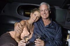 Lyckliga par med Champagne Sitting In Limousine Arkivbild