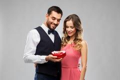 Lyckliga par med chokladasken i form av hjärta royaltyfri foto