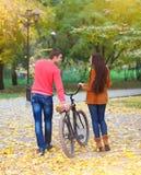 Lyckliga par med cykeln i höst parkerar Arkivbild