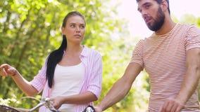 Lyckliga par med cyklar som talar på sommar, parkerar lager videofilmer