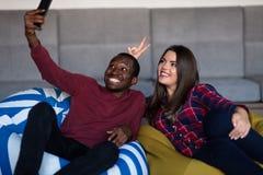 Lyckliga par med den datorminnestavlan och smartphonen p? en soffa royaltyfria bilder