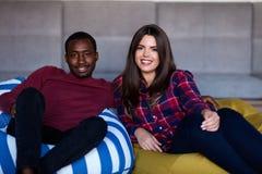 Lyckliga par med den datorminnestavlan och smartphonen p? en soffa royaltyfri fotografi