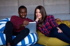 Lyckliga par med den datorminnestavlan och smartphonen p? en soffa fotografering för bildbyråer