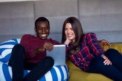Lyckliga par med den datorminnestavlan och smartphonen p? en soffa royaltyfri foto