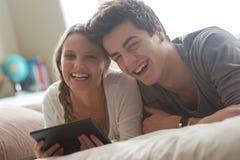 Lyckliga par med den digitala minnestavlan Royaltyfri Bild