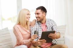 Lyckliga par med den minnestavlaPC och kreditkorten Arkivfoton