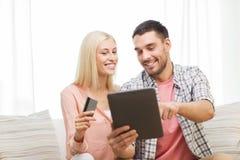 Lyckliga par med den minnestavlaPC och kreditkorten Royaltyfria Foton