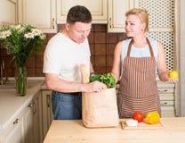 Lyckliga par med den pappers- påsen för livsmedelsbutik med grönsaker i kök arkivfoto
