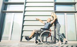 Lyckliga par med den rörelsehindrade mannen som omkring hänger på stads- stadsbakgrund - förhållandebegrepp inom handikappfrågor royaltyfri bild