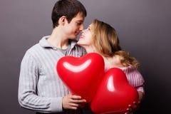 Lyckliga par med den röda ballongen. Valentindag Arkivbilder