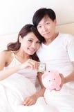 Lyckliga par med den rosa spargrisen Arkivbild