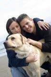 Lyckliga par med deras hund Royaltyfri Bild