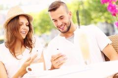 Lyckliga par med deras smartphones i ett kafé Fotografering för Bildbyråer