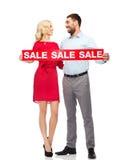 Lyckliga par med det röda försäljningstecknet Arkivfoton