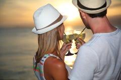Lyckliga par med drinkar som tycker om solnedgångsikt på havet arkivfoton