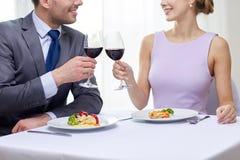 Lyckliga par med exponeringsglas av vin på restaurangen Arkivfoto
