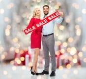 Lyckliga par med försäljning undertecknar över julljus Arkivbild