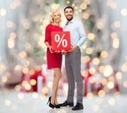 Lyckliga par med försäljning undertecknar över julljus Arkivbilder