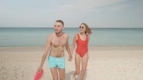 Lyckliga par med frisbeen på stranden stock video