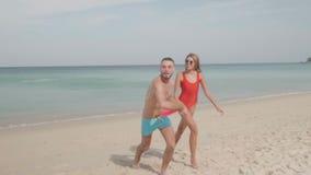 Lyckliga par med frisbeen på stranden arkivfilmer