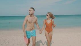 Lyckliga par med frisbeen på stranden lager videofilmer