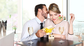Lyckliga par med gåvasammanträde på en tabell med vin royaltyfri fotografi