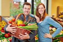 Lyckliga par med grönsaker i supermarket Royaltyfria Foton