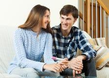 Lyckliga par med graviditetstestet Arkivfoto