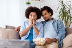 Lyckliga par med hållande ögonen på tv för popcorn hemma Fotografering för Bildbyråer