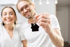 Lyckliga par med hem- tangent inomhus arkivbilder
