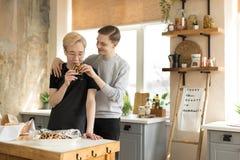 Lyckliga par med hemmastatt kök för coffe Stiliga homosexuella mäns dricka coffe royaltyfria bilder