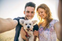 Lyckliga par med hunden Arkivfoto