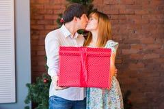 Lyckliga par med jul och gåvan för nytt år hemma familj som tillsammans ler jul min version för portföljtreevektor Arkivbilder