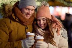 Lyckliga par med kaffe över julljus Royaltyfria Foton