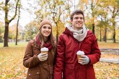 Lyckliga par med kaffe som går i höst, parkerar royaltyfria bilder