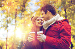 Lyckliga par med kaffe som går i höst, parkerar Arkivbilder