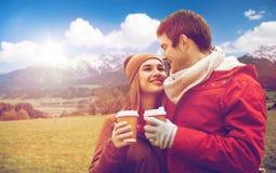 Lyckliga par med kaffekoppar över fjällängberg Royaltyfri Foto