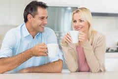 Lyckliga par med kaffekoppar i kök Royaltyfria Foton