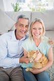 Lyckliga par med kattsammanträde i vardagsrum Royaltyfria Bilder