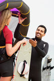 Lyckliga par med kiteboard på på sommardag Fotografering för Bildbyråer