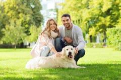 Lyckliga par med labrador dog att gå i stad Royaltyfri Bild