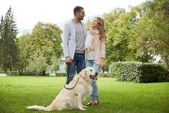 Lyckliga par med labrador dog att gå i stad Royaltyfria Bilder