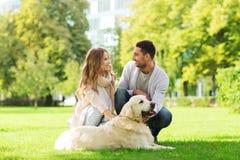 Lyckliga par med labrador dog att gå i stad Royaltyfri Fotografi