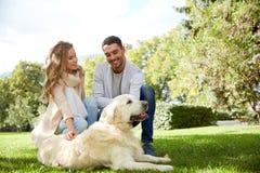 Lyckliga par med labrador dog att gå i stad Arkivbild
