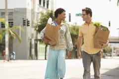 Lyckliga par med livsmedel som går på gatan Arkivfoton