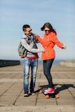 Lyckliga par med longboardridning utomhus royaltyfria foton