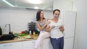 Lyckliga par med minnestavladatoren i kök hemma lager videofilmer