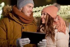Lyckliga par med minnestavlaPC på jul marknadsför Arkivfoto