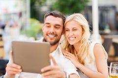 Lyckliga par med minnestavlaPC på restaurangen är slö Arkivfoto