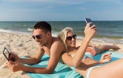 Lyckliga par med moderna grejer som ligger på stranden Royaltyfria Bilder